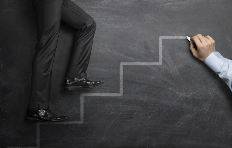 Businessman climbing the career steps drawn on a black chalkboard